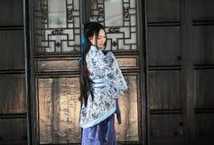 Stående av den asiatiska kinesiska flickan i traditionell klänning, blå och vit porslinstil Hanfu, ställning för kläder vid en dö Arkivfoto