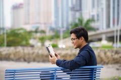 Stående av den asiatiska kontorsarbetaren med ipad på bänk Arkivfoton