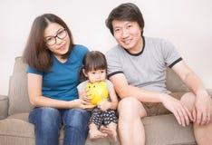 Stående av den asiatiska lyckliga familjen med en spargris Royaltyfri Fotografi