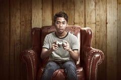 Stående av den asiatiska mannen som spelar videospel royaltyfria bilder