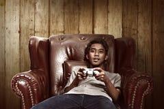 Stående av den asiatiska mannen som spelar videospel fotografering för bildbyråer