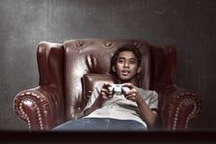 Stående av den asiatiska mannen som spelar videospel royaltyfri fotografi