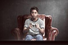 Stående av den asiatiska mannen som spelar videospel arkivbilder