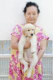 Stående av den asiatiska pensionären med valpen Fotografering för Bildbyråer