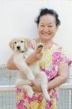 Stående av den asiatiska pensionären med valpen Arkivfoton