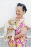Stående av den asiatiska pensionären med valpen Royaltyfri Foto