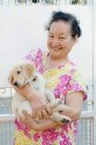 Stående av den asiatiska pensionären med valpen Royaltyfri Fotografi
