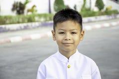 Stående av den asiatiska pojken som bär en vit skjorta på vägen arkivfoton