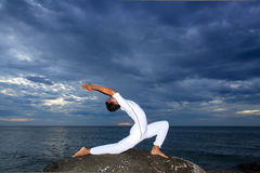 Stående av den asiatiska unga mannen som gör yoga på stenen Royaltyfri Foto