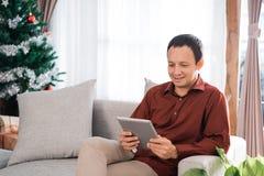 Stående av den asiatiska unga mannen som sitter på en soffa som rymmer ett digitalt royaltyfri bild