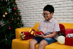 Stående av den asiatiska ungen som rymmer många gåvaaskar efter parti royaltyfri foto