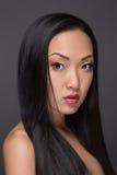 Stående av den attraktiva asiatiska kvinnan på grå bakgrund Arkivfoton