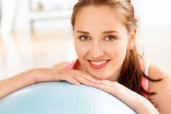 Stående av den attraktiva avslappnande konditionbollen för ung kvinna på idrottshallen Arkivfoto