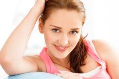 Stående av den attraktiva avslappnande konditionbollen för ung kvinna på idrottshallen Arkivbilder