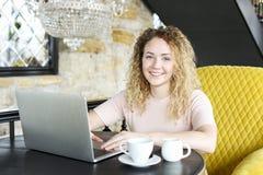 Stående av den attraktiva blonda unga kvinnan och att sitta i coffee shop som ler maskinskrivning på bärbara datorn för tom skärm arkivbild