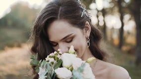 Stående av den attraktiva bruden som ler och sniffar blommor på kameran arkivfilmer