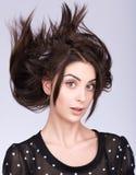 Stående av den attraktiva brunetten med flyghår Royaltyfri Bild
