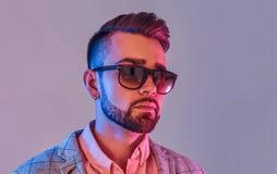Stående av den attraktiva eftertänksamma mannen i checkeretblazer och solglasögon arkivfoton