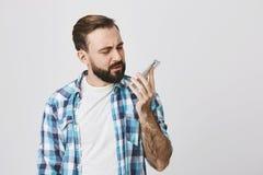 Stående av den attraktiva europeiska mannen med stilfull frisyr och skägget som ser smartphonen med förvirring, medan rymma den Royaltyfri Fotografi