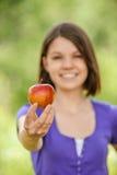 Stående av den attraktiva flickan som äter äpplet Fotografering för Bildbyråer