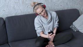 Stående av den attraktiva kvinnan som använder den smarta telefonen för att lyssna till musik stock video