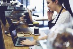 Stående av den attraktiva kvinnliga baristaen som arbetar i kafeteria Arkivfoton