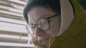 Stående av den attraktiva le unga kvinnan i exponeringsglas som är nära upp framsida av den lyckliga kvinnlign, positiva sinnesrö arkivfilmer