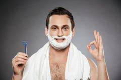 Stående av den attraktiva mannen med att raka skum på hans framsidainnehav Arkivfoton