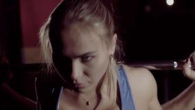 Stående av den attraktiva muskulösa kvinnan som förbereder sig till skivstångdeadliftövningen stock video