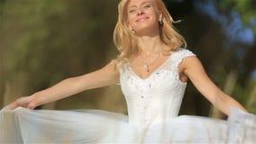 Stående av den attraktiva unga blonda banhoppningen och att le för brud i ett vetefält i solig sommardag gifta sig för trappa för stock video