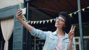 Stående av den attraktiva unga brunetten som tar selfieoutdoos med smartphonen stock video