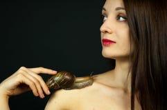 Stående av den attraktiva unga flickan med den stora snigeln på skuldra på svart bakgrund i studio royaltyfri fotografi