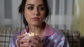 Stående av den attraktiva unga kvinnan som dricker varm choklad med marshmallower och watchinigfilmen i afton förhållande stock video