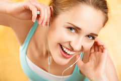 Stående av den attraktiva unga kvinnan som lyssnar till musik på idrottshallen fotografering för bildbyråer