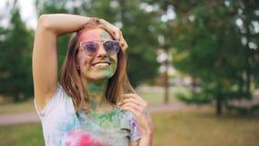 Stående av den attraktiva unga kvinnan som täckas med färgrik målarfärg på den Holi festivalen som ler och att se kameran och att lager videofilmer