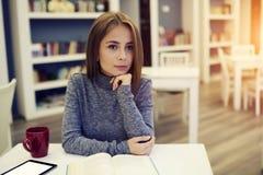 Stående av den attraktiva unga kvinnan som tänker över täppa av att tycka om för bok Arkivfoton