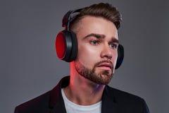 Stående av den attraktiva unga mannen i trådlös hörlurar som är lyssnande musik arkivbild