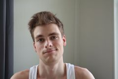 Stående av den attraktiva unga mannen med tillfredsställt uttryck Vit bakgrund emotionell stående klar hud och kort hår Barn royaltyfri fotografi