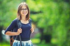 Stående av den attraktiva unga tonårs- skolaflickan med ryggsäcken arkivbild