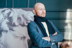 Stående av den attraktiva vuxna lyckade skalliga historiker för mankonstkritiker med skägget i halsduk i konstgalleri royaltyfri bild