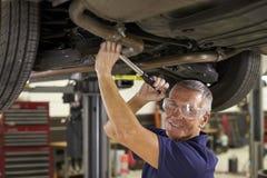 Stående av den auto mekanikern Working Underneath Car i garage arkivbild