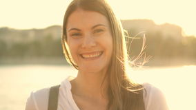 Stående av den avslappnande lyckliga gladlynta unga kvinnan utomhus Härlig flicka som ser kameran och att le lager videofilmer
