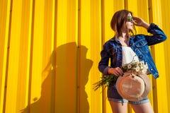 Stående av den bärande exponeringsglas och hatten för hipsterflicka med blommor mot gul bakgrund Sommardräkt Mode avstånd arkivfoto