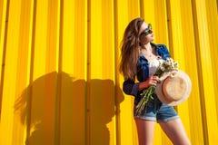 Stående av den bärande exponeringsglas och hatten för hipsterflicka med blommor mot gul bakgrund Sommardräkt Mode avstånd arkivbild