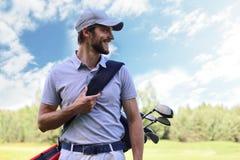 Stående av den bärande golfpåsen för manlig golfare, medan gå vid grönt gräs av golfklubben arkivbilder