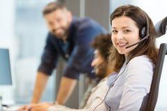 Stående av den bärande hörlurar med mikrofon för ung affärskvinna med kollegor i bakgrund på kontoret Royaltyfria Foton