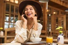 Stående av den bärande hatten för avkopplad kvinna som talar på smartphonen royaltyfri bild