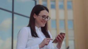 Stående av den bärande vita skjortan för affärskvinna genom att använda en smart telefon och smsa massage nära kontor Ultrarapids arkivfilmer