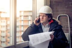 Stående av den bekymrade orakade byggmästaren som berättar vid mobilen, medan hålla olika projekt i hand Kommunikation och royaltyfri foto