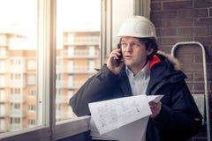 Stående av den bekymrade orakade byggmästaren som berättar vid mobilen, medan hålla olika projekt i hand Kommunikation och royaltyfria bilder